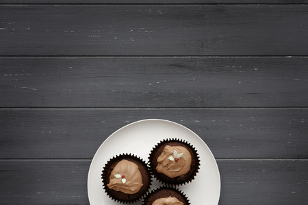 A white plate with  3 chocolate fairy cakes on a distressed wooden background, shot from above, with space for copy