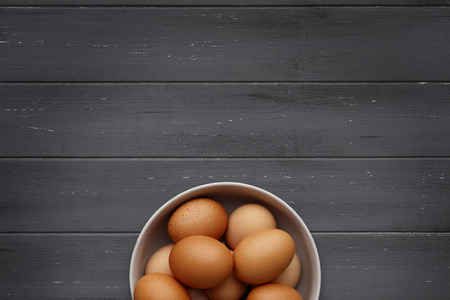 A bowl of fresh eggs on a distressed wooden background, shot from above, with space for copy 版權商用圖片
