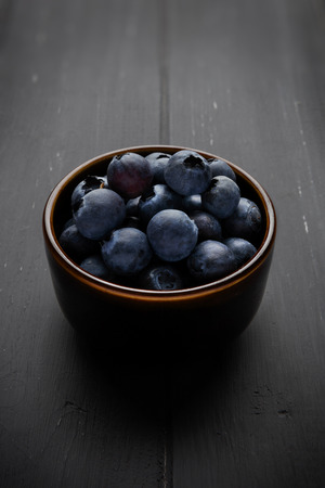 45 degree angle view of blueberries in a bowl and on dark grey wooden background