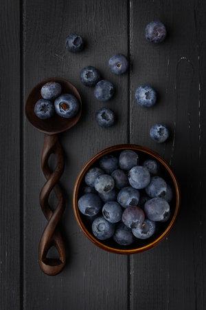blueberries in a bowl and wooden spoon on dark grey wooden background