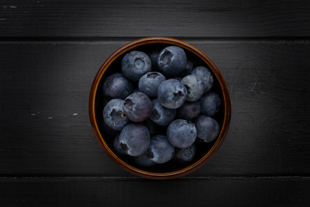 blueberries in a bowl on dark grey wooden background