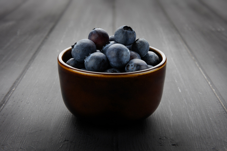 andscape shot of a 45 degree view of blueberries in a bowl and on dark grey wooden background