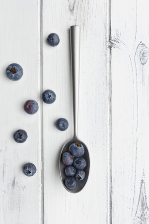 blueberries and a silver spoon on a distressed white wooden background