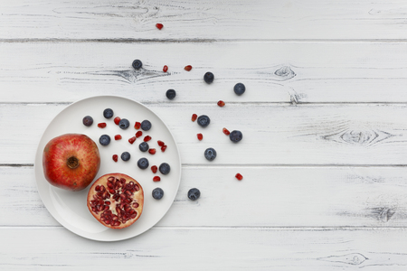 blueberries and pomegranate on a plate on a distressed white wooden background 版權商用圖片