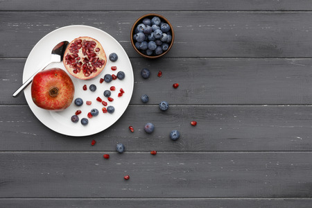 blueberries and pomegranate with a silver spoon on a plate on dark grey wooden background Imagens