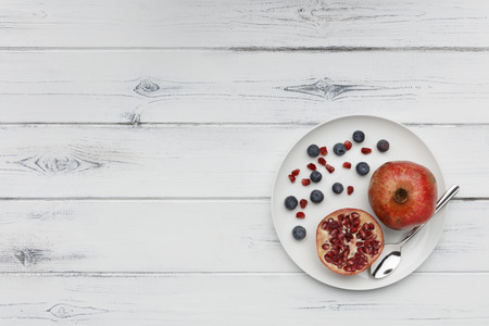 blueberries and pomegranate with a silver spoon on a plate ona  distressed white wooden background Stockfoto