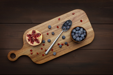 blueberries and pomegranate with a silver spoon on wooden chopping board, on a wooden background 版權商用圖片