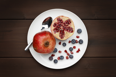 blueberries and pomegranate with a silver spoon on white plate on a wooden background 版權商用圖片