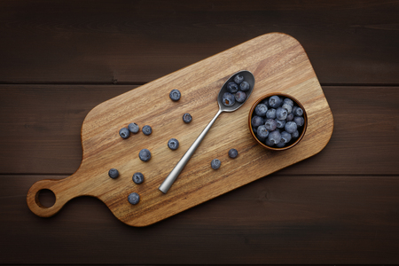 blueberries and silver spoon on a wooden chopping board on a wooden background