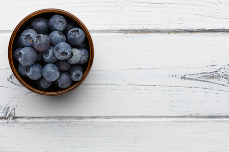 blueberries in a bowl on a distressed white wooden background with space for copy 版權商用圖片