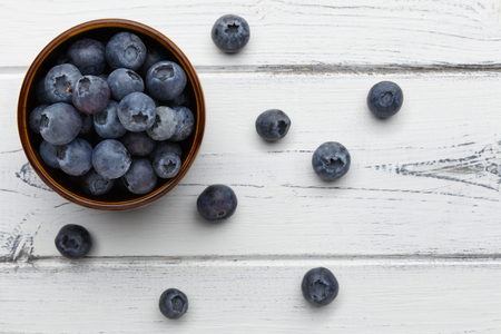 blueberries spilling out of a bowl on distressed white wooden background 版權商用圖片