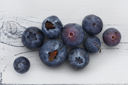 close up of blueberries on a distressed white wooden background