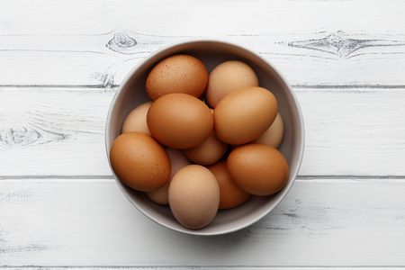fresh eggs in a bowl on a distressed white wooden background