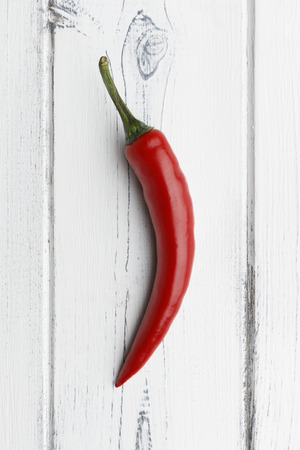 single red chilli on a distressed white wooden background Banco de Imagens
