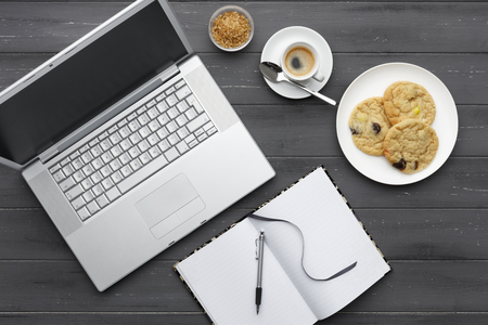 working coffee break with laptop, coffee, cookies and note pad on a dark wooden background
