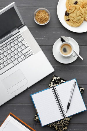 portrait view of a working coffee break with laptop, coffee, cookies, sugar and multiple note pads on a dark wooden background