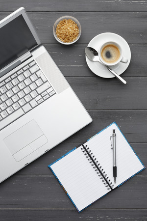portrait view of a working coffee break with laptop, coffee sugar and note pad on a dark wooden background