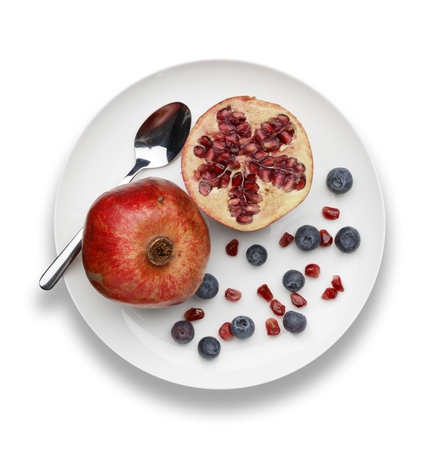 blueberries and pomegranate with a silver spoon on white plate on a white background 版權商用圖片