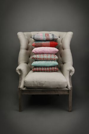 Armchair and a plie of colourful cushions on grey background