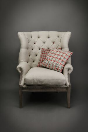 Armchair and 2 colourful cushions on grey background Foto de archivo