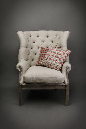 Armchair and 2 colourful cushions on grey background Reklamní fotografie