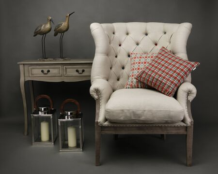 Armchair and 2 cushions  with side table with ornaments on grey background Reklamní fotografie