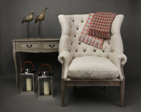 Armchair and 2 throws with side table with ornaments on grey background Reklamní fotografie