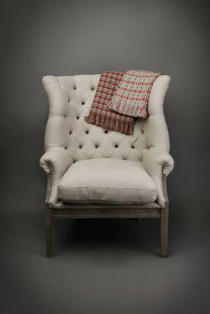 Armchair and 2 colourful throws on grey background