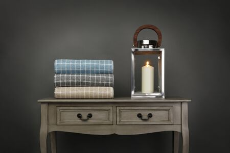 Side board table, candle and a pile of throws on grey background Reklamní fotografie