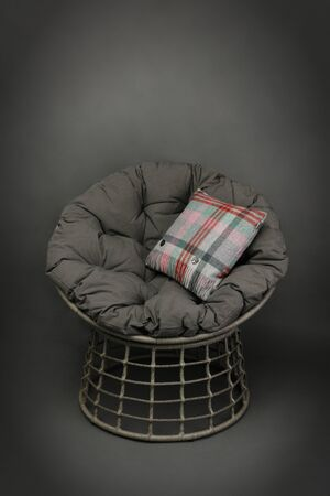 Wicker chair and soft seating cushion and a colourful cushion on grey background