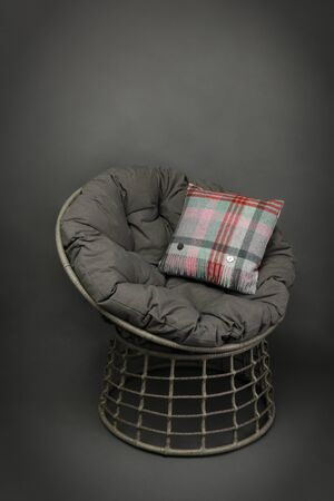side on view of a wicker chair and soft seating cushion and a colourful cushion on grey background