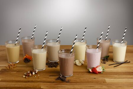 Glasses of various types of colourful milkshake with paper straws and ingredients on a wooden table top Reklamní fotografie