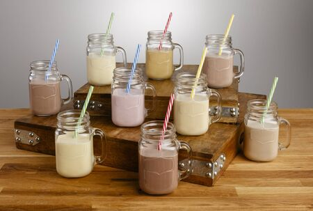 Various types of colourful milkshake in Mason Jar glasses with paper straws on a wooden table top