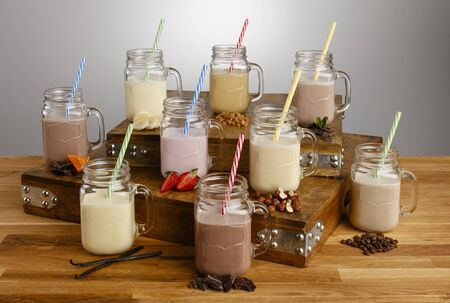 Various types of colouful milkshake and ingredients in Mason Jar glasses with paper straws on a wooden table top Reklamní fotografie