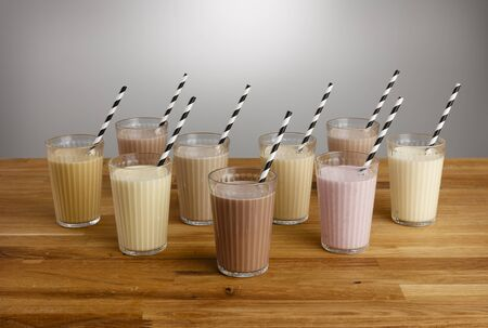 Glasses of various types of colourful milkshake with paper straws on a wooden table top Reklamní fotografie