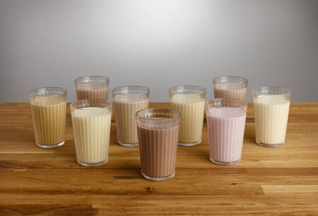 Glasses of various types of colourful milkshake on a wooden table top