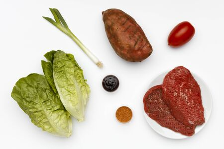 Raw ingredients for barbecued steak with vegetables and sauces shot on white.