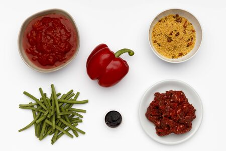 Raw ingredients for a bowl of a delicious Chipolte Meat Balls and couscous with vegetables and spices  shot on white.