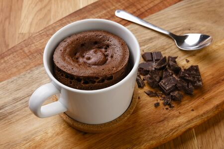 Delicious chocolate sponge pudding shot on a wooden board with a hand full of fudge pieces, in a cup with a spoon. Reklamní fotografie