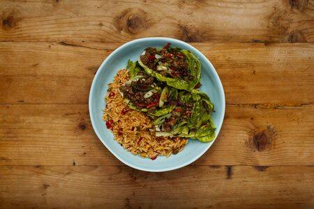 A bowl of succulent Spicy Beef Lettus Wraps on a bed of rice in a blue bowl shot on a wooden background Reklamní fotografie
