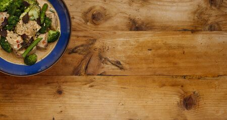A blue bowl of succulent Thai Red Chicken Curry shot a wooden background from above in a banner format