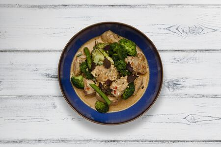A blue bowl of succulent Thai Red Chicken Curry shot a distressed white wooden background from above Reklamní fotografie