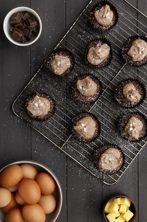 Fairy cakes on a cooling tray with a dusting of icing sugar and   ingredients, on a distressed grey wooden background, shot from above