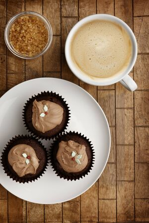 A Plate containing 3 chocolate fairy cakes and a cup of coffee with brown sugar on a wooden background, shot from above