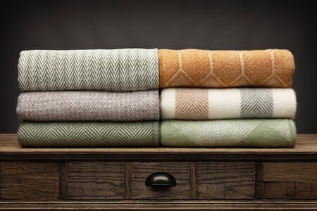 6 luxury throws, folded up and shot on a wooden sideboard, above a draw, with a grey background