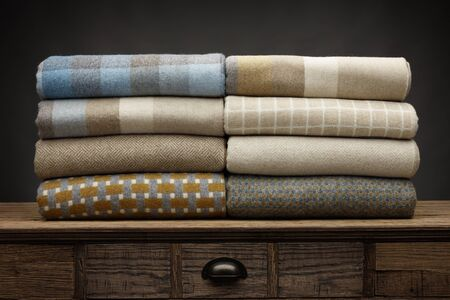 8 folded luxury throws shot on a wooden sideboard, above a draw, with a grey background