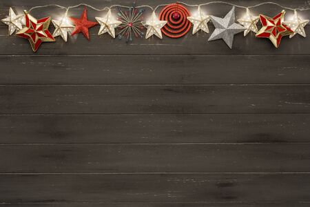 A string of golden star lights, and christmas star decorations, forming a banner with copy space on a destressed dark woodern background