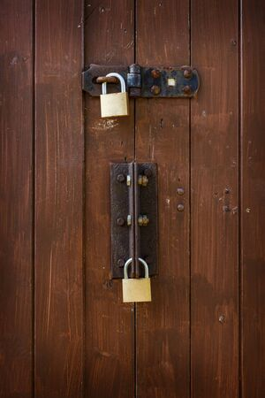 Rusty padlocks and locking bar on an old brown wooden panelled door
