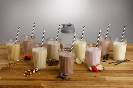 Glasses of various types of colourful milkshake with paper straws and ingredients on a wooden table top