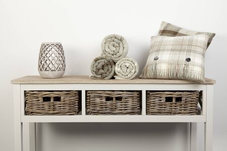 Sideboard style white wooden table with natural coloured cushions, throws and ornaments and wicker baskets on a white background